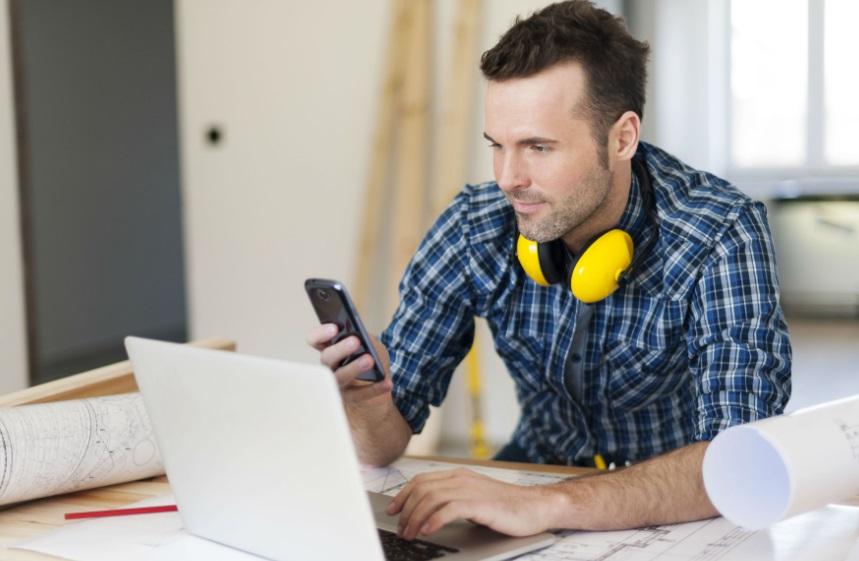 Homme devant un ordinateur et casque de chantier